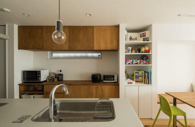 オーダーメイドのカップボードに裸電球のペンダントライトのあるキッチン