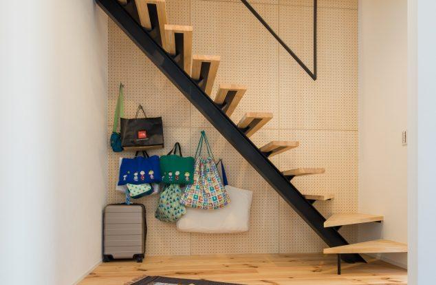 階段の奥に有孔ボードの壁がある玄関