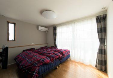 大きな掃き出し窓があり、ベッド後ろに腰壁をふかした寝室