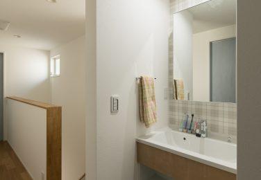 アクセントクロスと広く取った洗面ボールのある洗面台