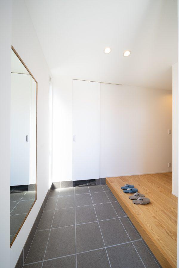 大きな鏡とシューズクロークとウォークインクローゼットが並ぶ玄関
