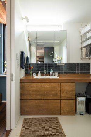 大きな一面鏡とタイルのおしゃれな洗面所